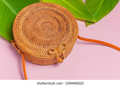 Fashionable handmade natural round rattan bag and tropical leaves on pink background flat lay. Top view with copy space. Trendy bamboo bag Ecobags from Bali. Summer fashion concept Tropical background