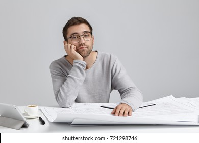 Fashionable handsome guy with bristle, wears spectacles, sits at working place, being overworked, surrounded with blueprints and modern gadget, keeps hand on cheek as wants to sleep or have rest