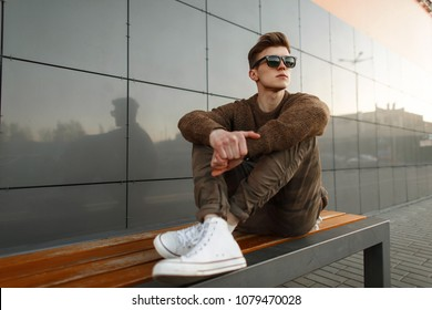 Fashionable handsome hipster man model with stylish sunglasses in a knitted sweater and military pants with white shoes sitting on a bench in the city