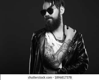fashionable handsome man in sunglasses. Brutal bearded Sexy boy in leather coat
