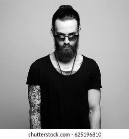 fashionable handsome man with tattoo and sunglasses. Brutal bearded Sexy boy in trendy glasses