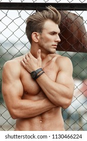 Fashionable handsome model man with a hairdo with a healthy sports body with muscles near the metal lattice