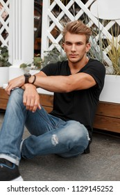 Fashionable handsome model man with a style in a black T-shirt and jeans sits near a wooden fence on the street