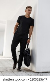 Fashionable handsome young man in black stylish clothes with a black bag posing near the white wall