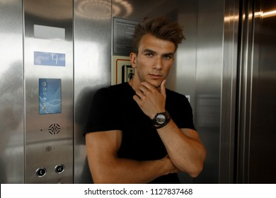 Fashionable handsome young man with a hairstyle in a black T-shirt in an elevator