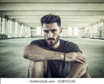 Fashionable Handsome Young Man Posing, Sitting on the Ground Inside an Empty Building While Looking at the Camera
