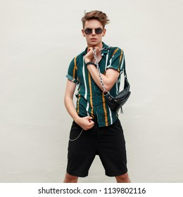 Fashionable handsome young man with sunglasses in beach shirt with bag posing near wall