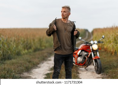 Fashionable handsome young model of a man in a khaki jacket with a T-shirt near a motorcycle will poses in a cornfield