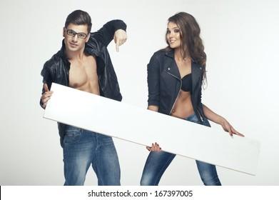 Fashionable happy pretty couple holding white board