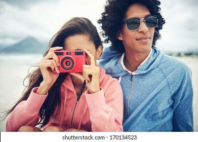 Fashionable hipster couple taking retro camera photo at beach