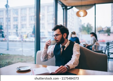 Fashionable hipster guy drinking hot coffee and looking at cafeteria window after reading interesting best seller, caucasian man pondering on literature during enjoying caffeine beverage indoors