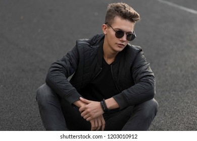 Fashionable hipster man in black stylish clothes sits on the street