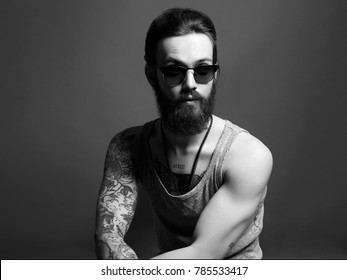 fashionable hipster man with tattoo and sunglasses. Brutal bearded Sexy boy in trendy glasses