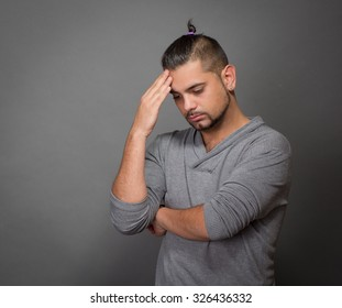 Fashionable hipster man touching his head and thinking attentively while posing for professional photographer in studio.