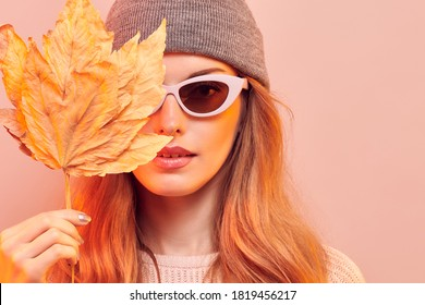 Fashionable hipster woman in Trendy autumn fall outfit, stylish hair, makeup. Redhead model in jumper, fashion jeans having fun smiling. Beautiful woman in autumnal beanie hat with maple leaf