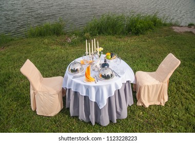 The fashionable holiday table outdoors on the banks of the river
