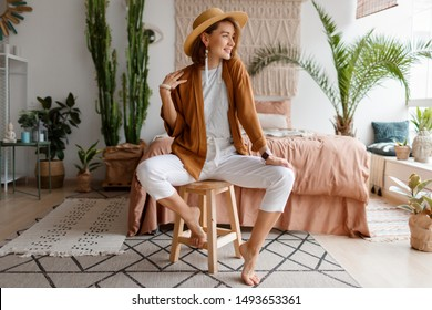 Fashionable image of happy woman in straw hat posing over bohemian interior background. Straw hat , limes closes. Natural make up.