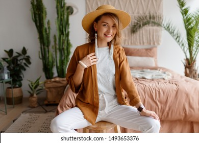 Fashionable image of happy woman in straw hat posing over bohemian interior background. Straw hat , linen  closes. Natural make up.