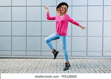 Fashionable image of inspired happy blonde woman with wavy hairstyle posing on grey urban  building wall. Wearing pink knitted sweater and  trendy jeans.