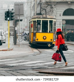 Fashionable Italian woman in Milan, Italy crossing street with traditional Milanese tram in background