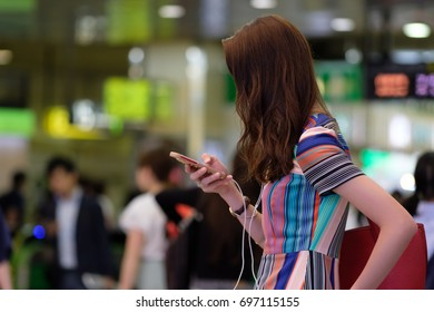 Fashionable Japanese woman using her smart phone in a busy railway station in Tokyo.