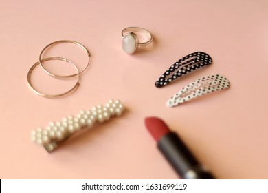 Fashionable jewelry, accessories and make-up on pink background: red lipstick, pearl beret, polkadot hair clips, silver hoop earrings and silver gemstone ring. Selective focus.