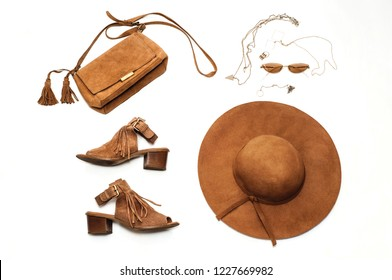 Fashionable lady. Brown suede sandals, hat, bag, glasses and jewelry on a white background. Flat lay