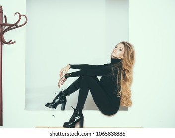 Fashionable lady with make up and skinny legs sit, white background. Girl with long curly hair on mysterious face, copy space. Fashion and beauty concept. Lady slim wears black fit clothes.