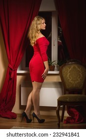 Fashionable lady in a red dress in the vintage interior