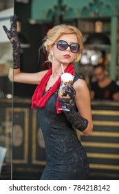 Fashionable  lady with short black lace dress and red scarf  and high heels, outdoor shot . Young attractive short haired blonde woman with sunglasses posing having a frappe coffee drink  outside