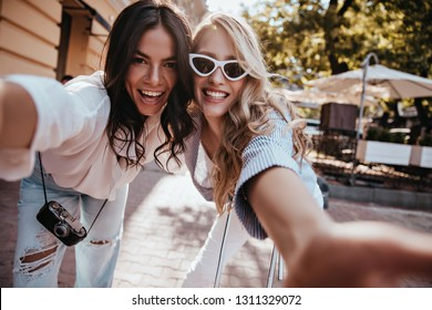 Fashionable latin girl making selfie with friend. Outdoor portrait of two cute ladies having fun together.