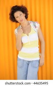 Fashionable Latina model with curly hair leaning on bright orange wall.