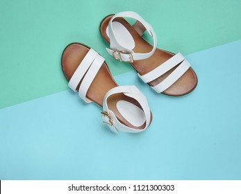 Fashionable leather women's sandals on a colored pastel background, summer shoes, top view, minimalism