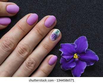 Fashionable lilac manicure design in the hand on a black background.