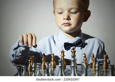 Fashionable Little boy playing chess.Smart kid.fashion children.5 Years Old Child in Bow-tie. Little genius Child. Intelligent game.Chessboard