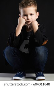 fashionable little boy.stylish kid is sitting in the studio with a black background.children