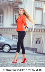 Fashionable look, hot day model of a young woman walking in the city, wearing a red jacket and black pants, blond hair fluttering outdoors over the city warm background.