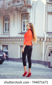 Fashionable look, hot day model of a young woman walking in the city, wearing a red jacket and black pants, blond hair outdoors over the city warm background.