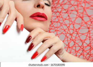 Fashionable makeup and manicure in dark red and light shades of nail Polish.Creative nail art on a young woman on a bound background.