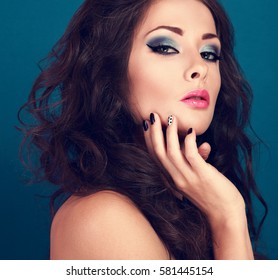 Fashionable makeup woman with long curly hair, creative manicured nails and bright eyeshadow on color background. Closeup. Perfect eyebrow and pink lipstick