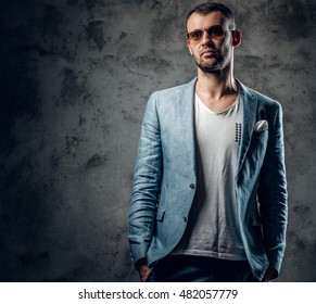 Fashionable male in azure jacket and sunglasses posing in a studio.