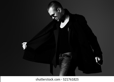 Fashionable male model wearing coat posing in motion. Men's beauty, seasonal collection. Black-and-white studio portrait.