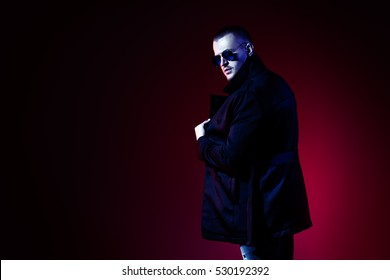 Fashionable male model wearing coat and sunglasses posing at studio over red background. Men's beauty, seasonal collection.
