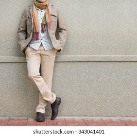 fashionable man in beige trousers and jacket against stone wall