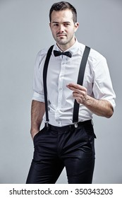 Fashionable man with bow tie and suspenders flicking fingers isolated over grey