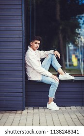 Fashionable man in a denim jacket and white shoes posing in urban style