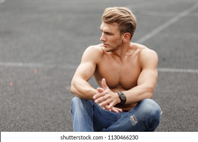 fashionable man with hairstyle with a fitness naked torso sits on the street on the asphalt