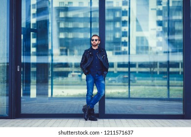 fashionable man in jeans and leather jacket posing on glass background