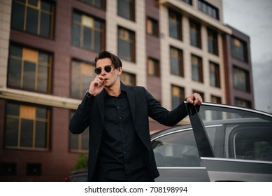 A fashionable man lurks beside the car and smokes a cigar.