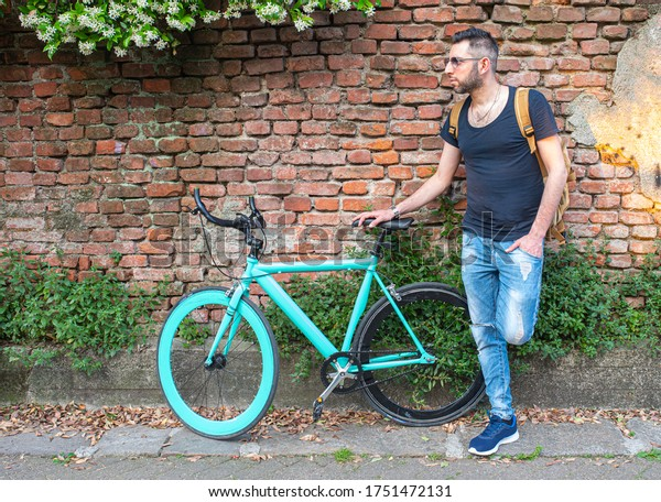 fashionable man portrayed next to his beautiful minimal bicycle, background of red and solid brick wall, fashionable and ecological urban transport concept